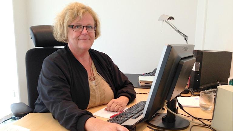 Turistchefen i Karlshamn, Lena Axelsson, sitter framför datorn på sitt kontor. Ljuset lyser in från fönstret bakom henne. Hon har ljust lockigt hår och svart kofta på sig.