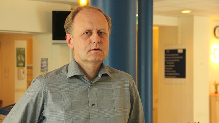 Bengt Wittesjö står i grårutig skjorta i entren till sjukhuset.