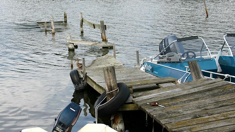 En rutten brygga med två båtar på varsin sida skruvar sig ner under vattenytan och delar av den försvinner under vattnet.