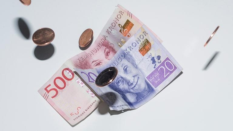 sedlar om mynt mot en vit bakgrund.