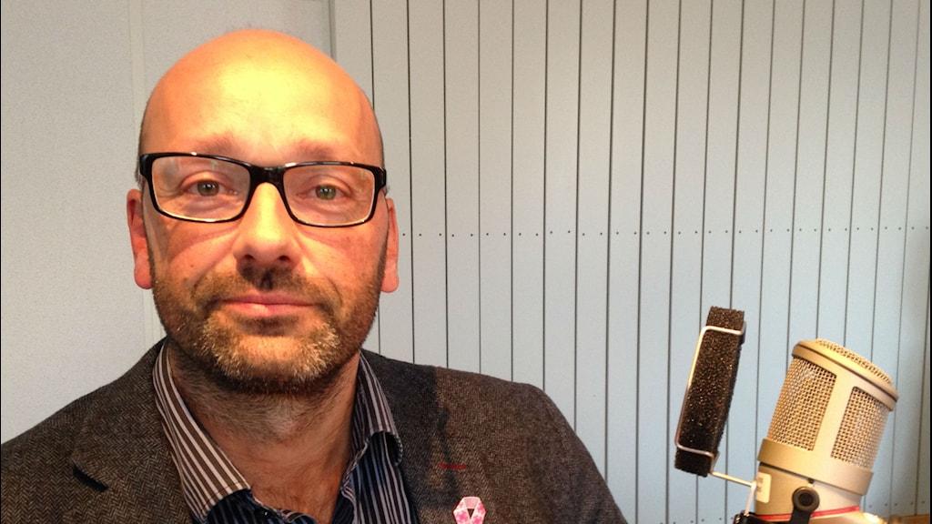 Robert Johannesson med glasögon med svarta bågar i tweedkavaj med rosa bandet på slaget. Foto: Jesper Cederstrand / Sveriges Radio