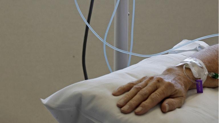 Bild på en hand med sladdar som får cancerbehandling.
