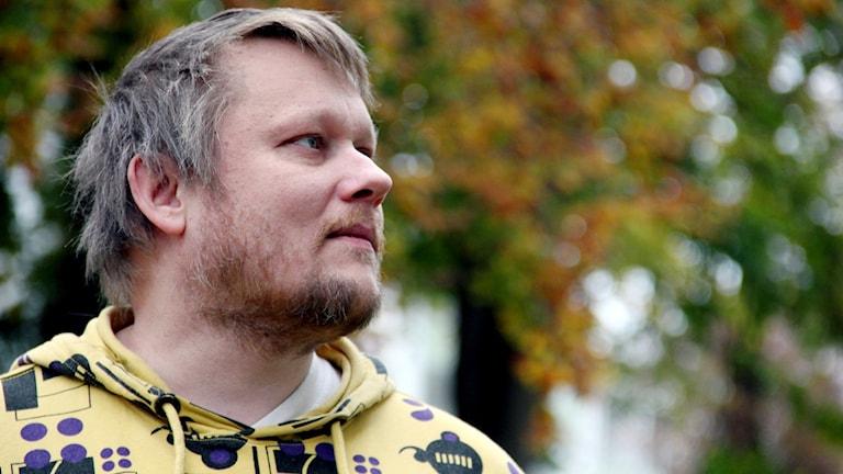 Mikk Jakola Står framför en höströd bokskog.  Foto: Stina Linde/Sveriges Radio