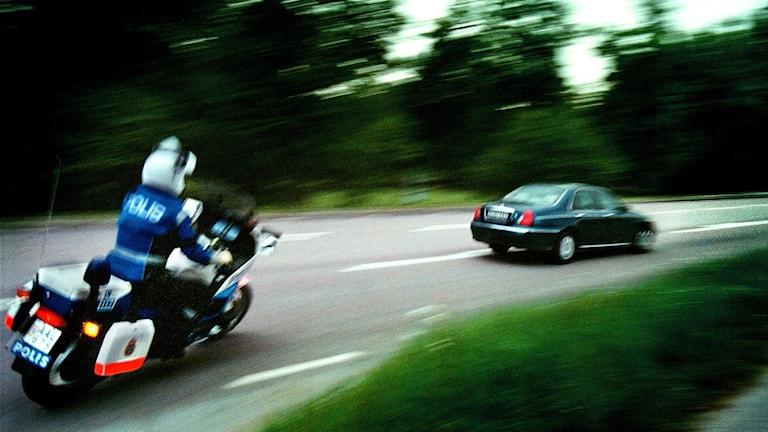 motorcykelpolis kör efter blå bil