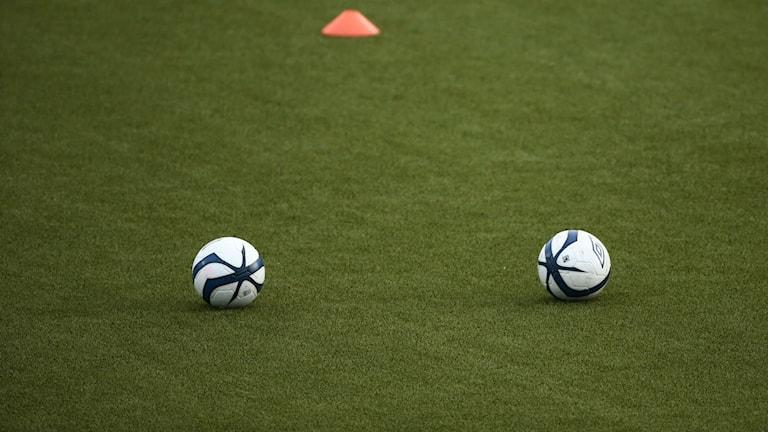 två fotbollar på gräs
