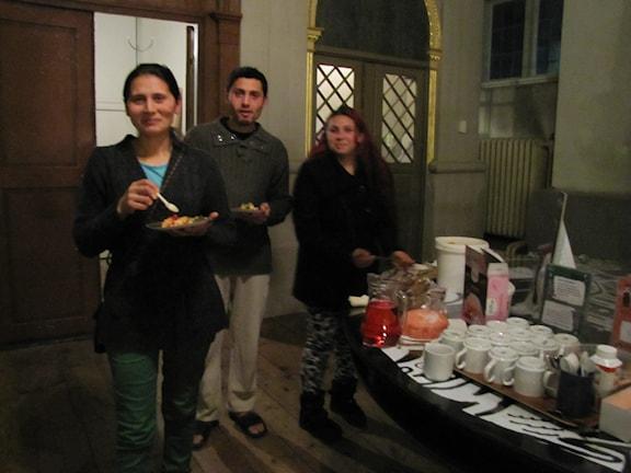 Tre rumänska tiggare äter mat i kyrkan.
