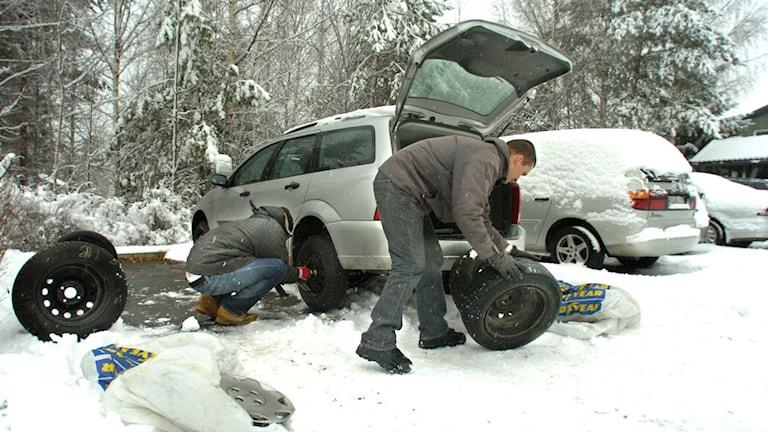 två män byter däck på bil