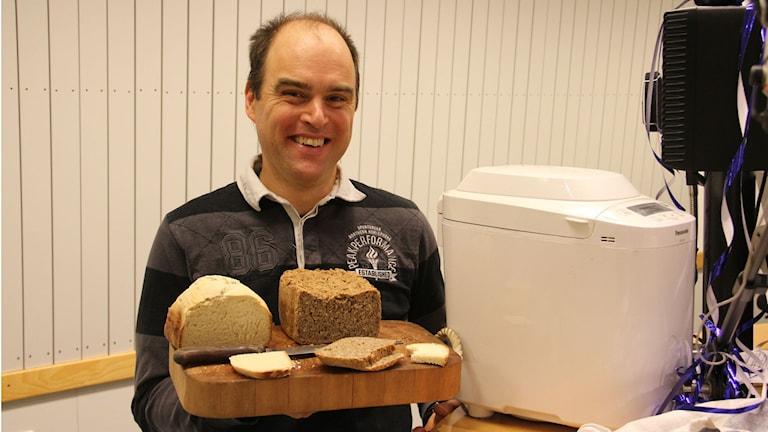Närbild på en man som håller upp två nybakta bröd. Foto: Rebecka Gyllin/Sveriges Radio