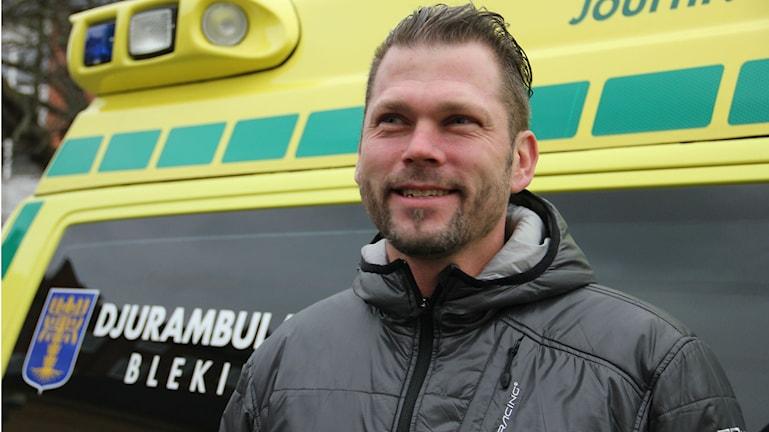 Närbild på en man som står framför en gul ambulans. Foto: Rebecka Gyllin/Sveriges Radio