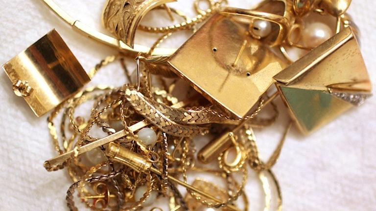 En hög med guldsmycken mot vit bakgrund. Foto: Steven Senne/TT