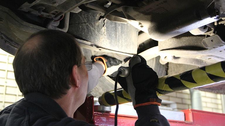 Besiktningsman lyser under en bil.