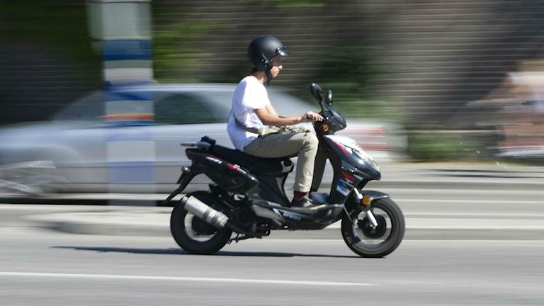 En kille sitter på en moped. Foto: Bertil Ericson/TT