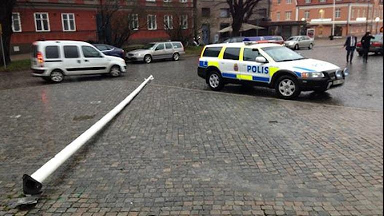 En flaggstång som ligger på marknen precis intill en polisbil. Foto: Sveriges Radio