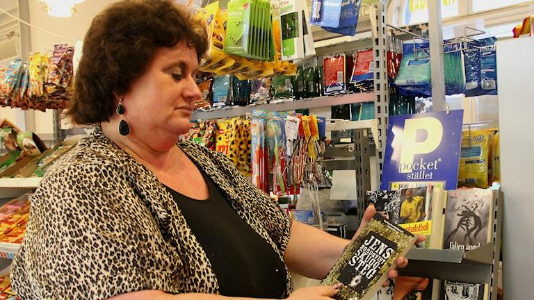 Susanne Andersson som jobbar i järnvägskiosken står framför att nästan tomt pockebokställ.