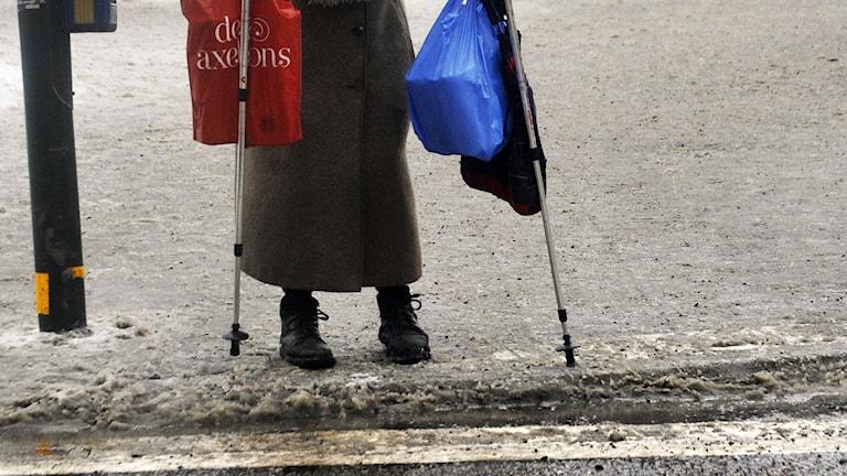 Äldre kvinna med stavar och kassar på väg över ett övergångsställe. Foto. Hasse Holmberg /