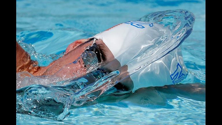 En man i badmössa som crawlar. Foto: TT