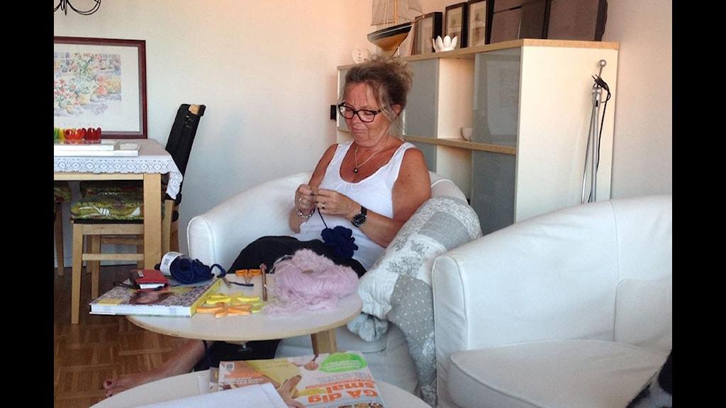 Gudrun Cahm sitter och virkar i en fåtölj. Foto: privat.
