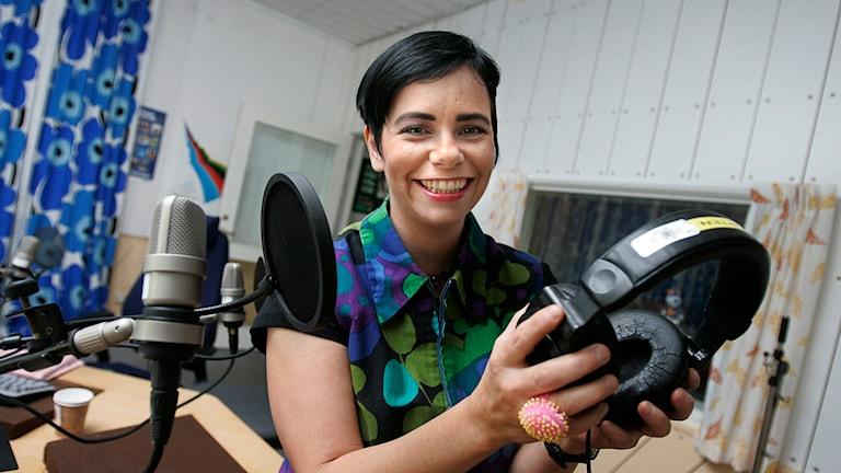 Programledaren Carolina Norén sitter med ett par hörlurar i handen. Foto: Jonas Ekströmer