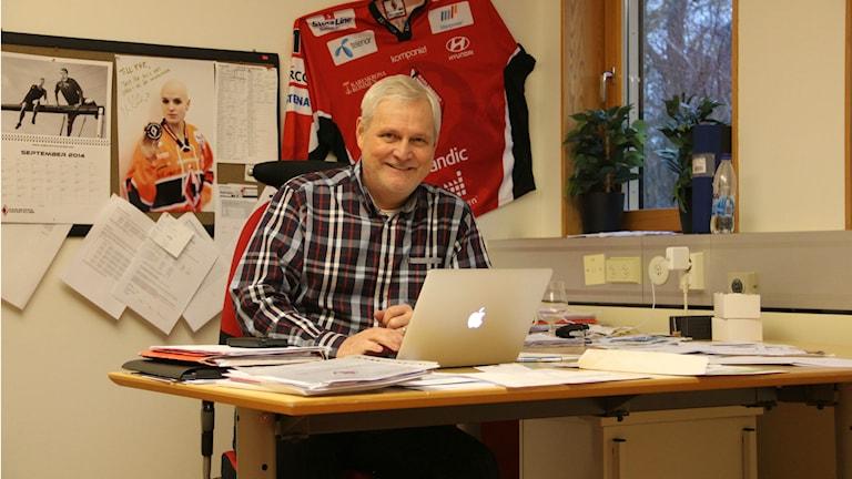 En man i rutig skjorta sitter vid ett skrivbord. Foto: Rebecka Gyllin/Sveriges Radio