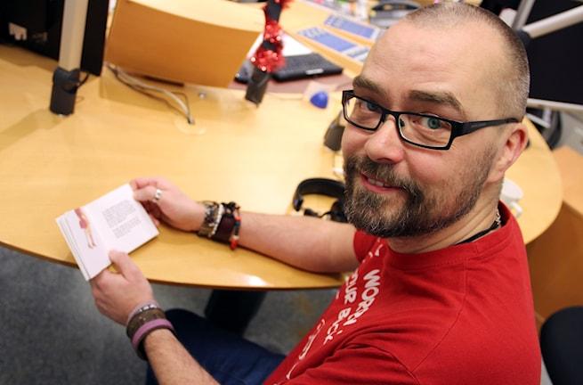 Micke Gunnarsson sitter och bläddrar i en liten Pixibok. Foto: Stina Linde/Sveriges Radio