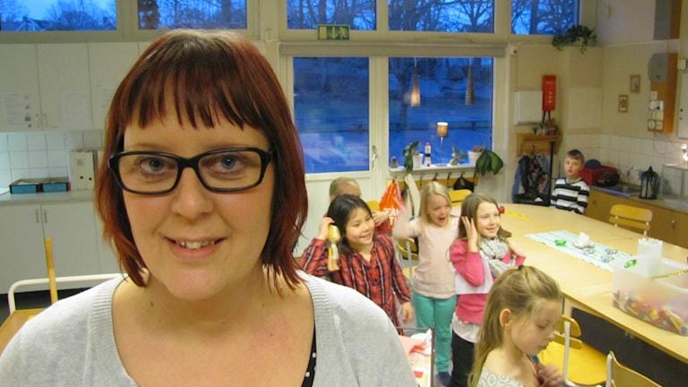 Maria Johansson framför ett gäng barn som gör gymnastik i bakgrunden. Foto: Jesper Cederstrand/Sveriges Radio