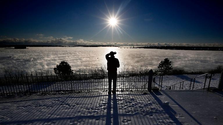 En man står i motljus på en snötäckt utegård. Foto: TT