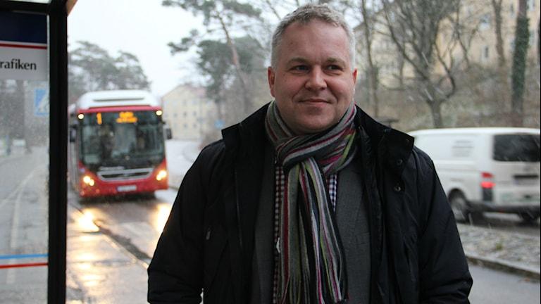 En man står vid en busskur, i bakgrunden syns en buss. Foto: Rebecka Gyllin/Sveriges Radio