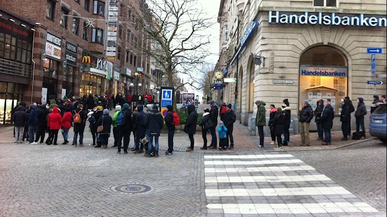 Många personer står i en lång kö. Foto: Mikael Eriksson/Sveriges Radio