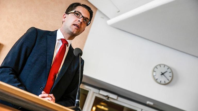 Sverigedemokraternas partiledare Jimmie Åkesson står vid ett bord. Foto: TT