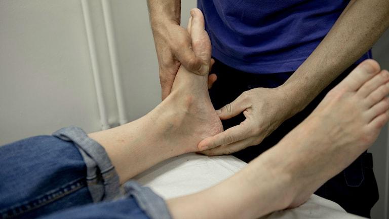 man blir behandlad av sjukgymnast för sina fötter.