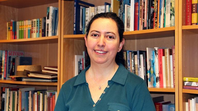 Cynthia Gonzalez-Gene står framför böcker i SR:s bibliotek. Foto: Annika Nilsson/Sveriges Radio.
