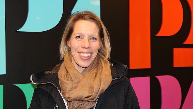 Löptränare Anna Johansson framför logga. Foto: Annika Nilsson/Sveriges Radio