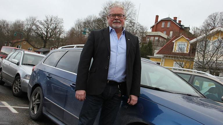 Näringslivschefen Torbjörn Lind framför en blå bil. Foto: Mikael Eriksson/Sveriges Radio