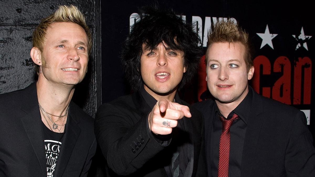 Bandet Green Day står framför en plansch. Foto: Charles Sykes/Scanpix