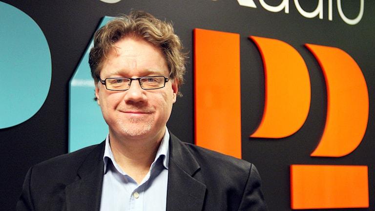 Centerpartisten och kommunalrådet Magnus Larsson står framför SR:s loggor. Foto: Annika Nilsson/Sveriges Radio.