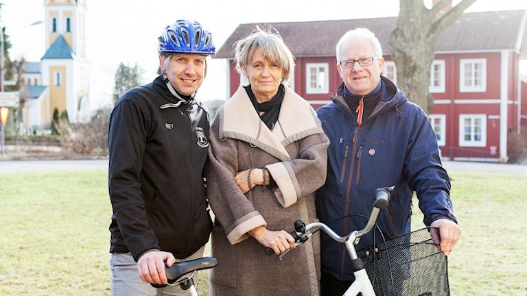 Tre personer poserar med en cykel.