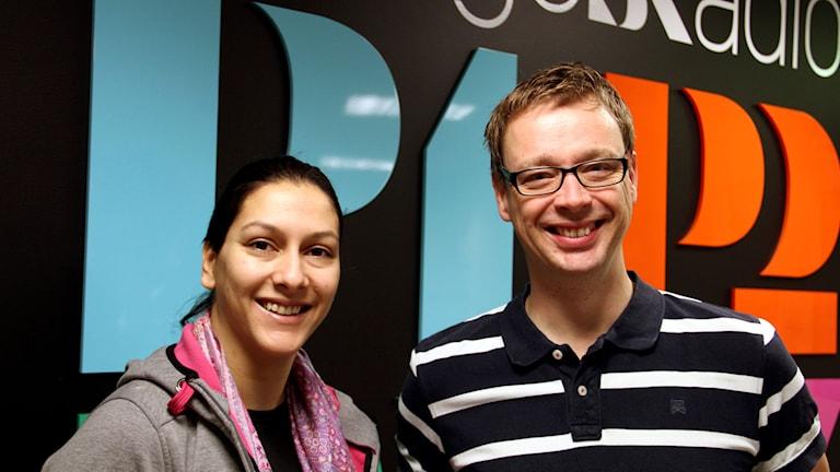 En kvinna och en man står framför Sveriges Radios loggor. Foto: Annika Nilsson/Sveriges Radio