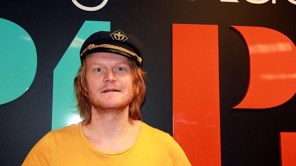 Lars Lindquist står framför SR:s loggor. Foto: Annika Nilsson/Sveriges Radio