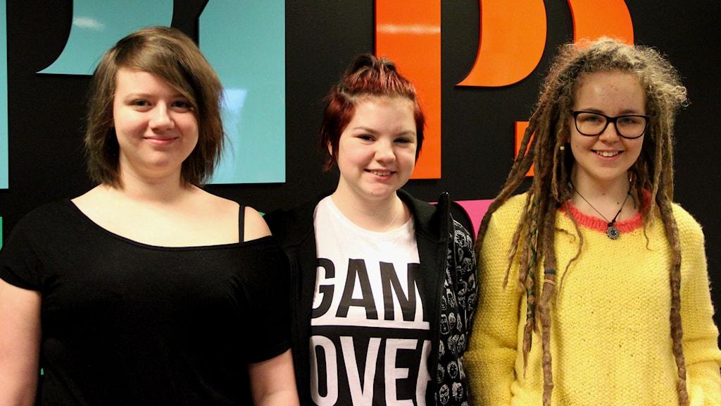 Tre tjejer framför SR:s loggor. Foto: Annika Nilsson/Sveriges Radio