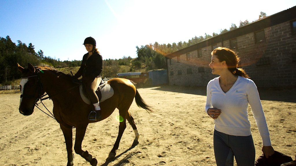 En tjej rider på en häst bredvid en ridlärare. Foto: Henrik Montgomery/TT