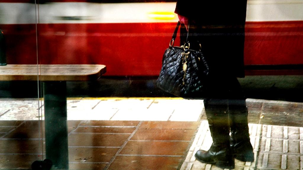 En kvinna med en handväska står vid en busshållplats. Foto: Hasse Holmberg/TT