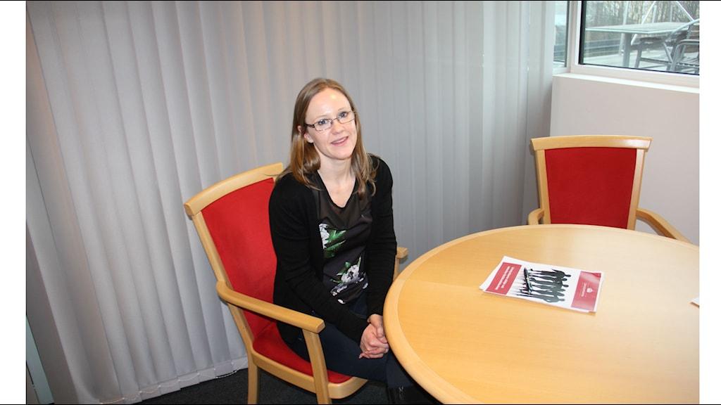 Annette Ludvigsson sitter vid sitt skrivbord på länsstyrelsen, framför henne ligger länsstyrelsens rapport om varierande stöd till tonårsföräldrar.