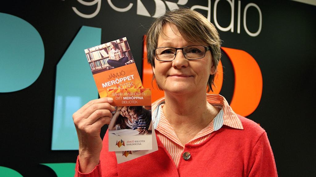 En kvinna står med två broschyrer framför SR:s loggor. Foto: Annika Nilsson/Sveriges Radio