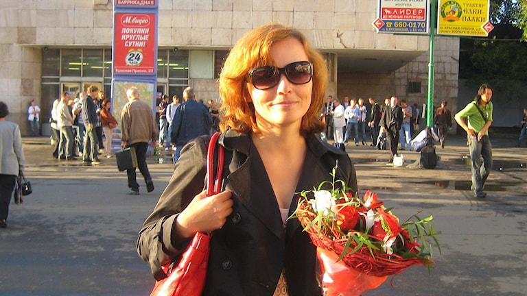 En kvinna håller i en blombukett. Foto: Privat
