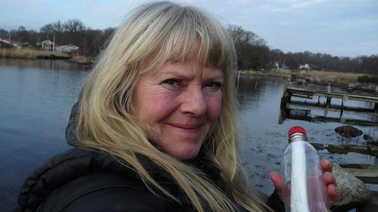 Eva Hall står med en flaskpost i handen vid havet.