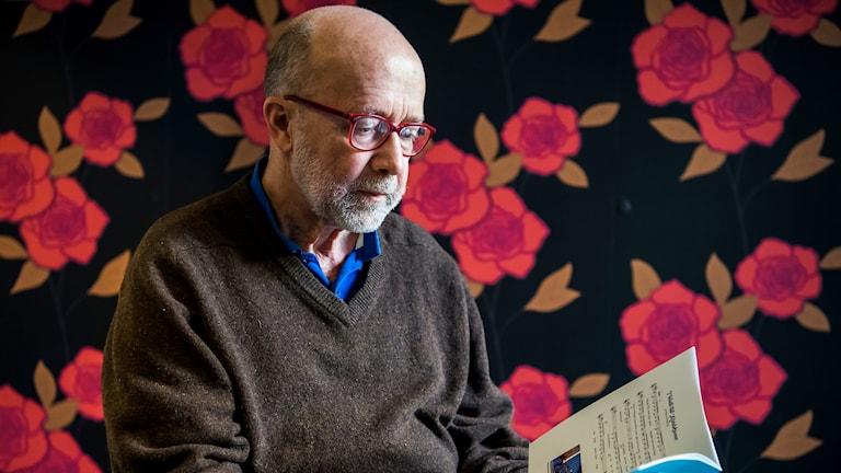 En bild där Mats Enqvist sitter med en bok i handen.