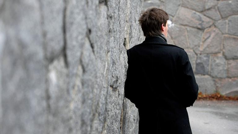 En man står och hänger mot en stenvägg. Foto: Janerik Henriksson/TT