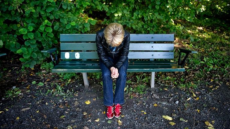 En person sitter med hängande huvud på en barkbänk. Foto: Jessica Goe/TT