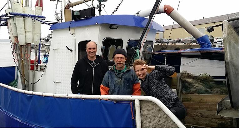 Tre personer står på en båt