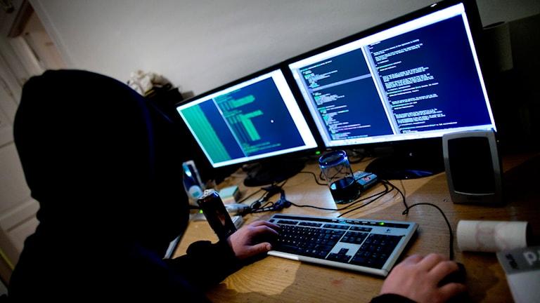 En huvklädd hackare och lysande datorer.